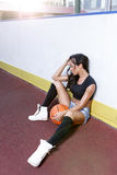 Beautiful brunette woman playing basketball on court outdoor Stock Image