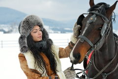 Beautiful brunette woman portrait with horse in winter Stock Image