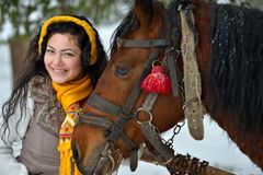 Beautiful brunette woman portrait with horse in winter Stock Images