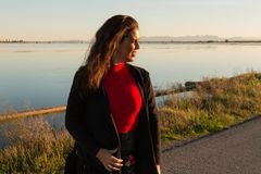 Beautiful brunette woman portrait standing outside in a sunny day, with a lake in background royalty free stock photo