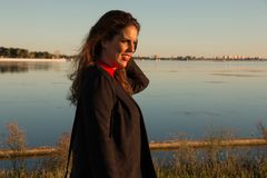 Beautiful brunette woman portrait standing outside in a sunny day, with a lake in background royalty free stock photos