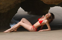 Beautiful brunette woman posing at the beach in red bikini. Leo Carillo beach, California Royalty Free Stock Image