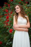 Beautiful brunette woman posing in a garden park in white long d stock photography