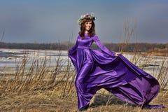 Beautiful brunette woman in purple long dress i Stock Image