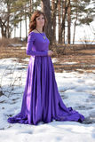 Beautiful brunette woman in purple long dress i Royalty Free Stock Images