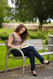 Beautiful brunette woman reading a book. A smiling beautiful brunette woman in her twenties sitting on a bench in a park and reading a book Stock Photos