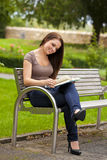 Beautiful brunette woman reading a book. A smiling beautiful brunette woman in her twenties sitting on a bench in a park and reading a book Stock Images