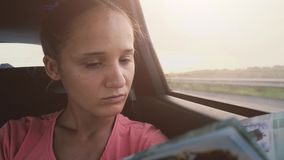 Pretty brunette woman reading a book while traveling in a car during sunset. slow motion. 3840x2160. Beautiful brunette woman reading a book while traveling in a stock video footage