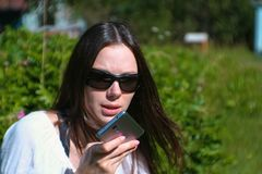Beautiful brunette woman records a voice message on her mobile phone while sitting in the park on a Sunny day. Beautiful brunette woman records a voice message stock images