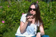 Beautiful brunette woman records a voice message on her mobile phone while sitting in the park on a Sunny day. Beautiful brunette woman records a voice message stock photo
