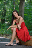 Beautiful brunette woman in red dress sitting on suitcase Royalty Free Stock Photos
