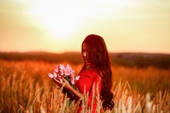 Beautiful brunette woman in red dress with tulips in hands on a Stock Images