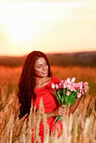 Beautiful brunette woman in red dress with tulips in hands on a Royalty Free Stock Images
