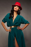 Beautiful brunette woman in red hat with red lipstick and turquoise evening dress with belt. Stock Photos