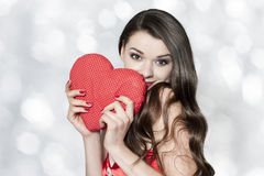 Beautiful brunette woman with red heart and shiny hair Stock Photo