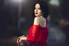 Beautiful brunette woman with red lips and dress. Portrait of a mysterious brunette beautiful woman with red lips and dress. He admires the sunset in the city Royalty Free Stock Photography