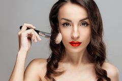 Beautiful brunette woman with red lipstick on lips. Close-up girl with beautiful make-up. royalty free stock image