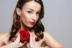 Beautiful brunette woman with red lipstick on lips. Close-up girl with rose. royalty free stock photo