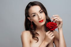 Beautiful brunette woman with red lipstick on lips. Close-up girl with rose. royalty free stock photography