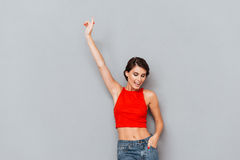 Beautiful brunette woman in red top pointing finger up Royalty Free Stock Images