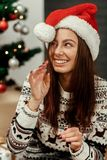 Beautiful brunette woman in reindeer warm sweater and red santa Royalty Free Stock Photography