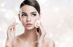 Beautiful brunette woman removing makeup from her face, skin care concept Stock Photos