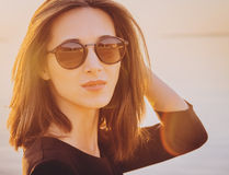 Beautiful brunette woman in round sunglasses. Portrait of beautiful brunette woman in round sunglasses on beach at sunny day. Image with sunlight effect stock photo
