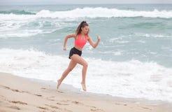 Beautiful brunette woman runs on the sand coastline at the morni Royalty Free Stock Photos