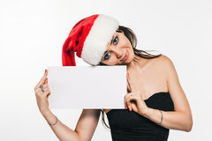 Beautiful brunette woman in Santa hat holding leaflet for messag Royalty Free Stock Image