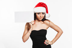 Beautiful brunette woman in Santa hat holding leaflet for messag Stock Photography