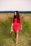 beautiful brunette woman with shoes in hand on a field Royalty Free Stock Photo