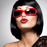 Beautiful brunette woman with shot hairstyle with red sunglasses Royalty Free Stock Photos