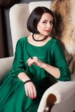 Beautiful brunette woman in a silk green dress posing sitting in a vintage chair. Bohemian style.  stock photos