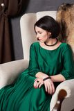 Beautiful brunette woman in a silk green dress posing sitting in a vintage chair. Bohemian style.  stock images