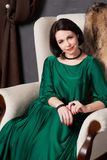 Beautiful brunette woman in a silk green dress posing sitting in a vintage chair. Bohemian style.  royalty free stock photos