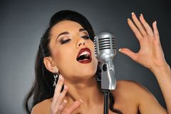Beautiful brunette woman singing Stock Photos