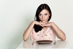 Beautiful brunette woman sitting with an empty plate and wait her lunch Stock Photography