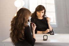 Beautiful brunette woman sitting at mirror and doing makeup Royalty Free Stock Photography