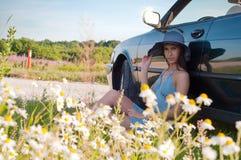 Beautiful brunette woman sitting near car royalty free stock image