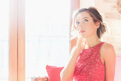 Beautiful brunette woman sitting near a sunny window Stock Image