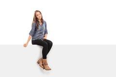 Beautiful brunette woman sitting on a panel Royalty Free Stock Image