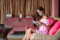 Beautiful brunette woman sitting on a pink sofa and reading a book and smiling. Interior in ethnic style. Close up stock images
