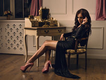 Beautiful brunette woman sitting on a retro chair in black dress. Beautiful brunette woman sitting on a retro chair in gorgeous luxury black dress Stock Photography