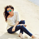 Beautiful brunette woman sitting on a sand Stock Photography