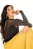 Beautiful brunette woman sitting wearing yellow skirt looking up Stock Photos