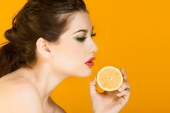 Beautiful brunette woman with slice of lemon. Gorgeous young woman wearing colorful make-up and holding slice of lemon Royalty Free Stock Photography