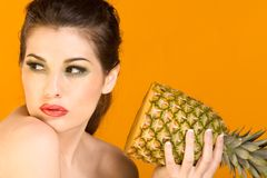 Beautiful brunette woman with slice of pineapple Royalty Free Stock Photography