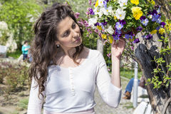 Beautiful brunette woman smelling fresh spring flowers in a blooming garden Royalty Free Stock Image