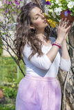 Beautiful brunette woman smelling fresh spring flowers in a blooming garden Royalty Free Stock Photo