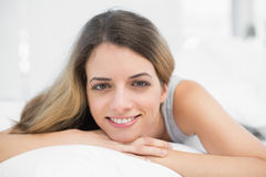 Beautiful brunette woman smiling at camera lying on her bed Royalty Free Stock Photo
